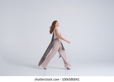 Side view of woman model walking in trend clothing