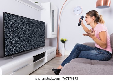 Side View Of A Woman On Sofa Frustrated With A TV Screen Glitch