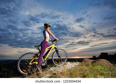 Side view woman with perfect figure on a bicycle on stone looking into the distance enjoying a superb blue sky with clouds and sun at sunset. In the background there is a city