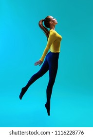 Side view of woman with ponytail wearing yellow jumper and blue leggings jumping on blue background