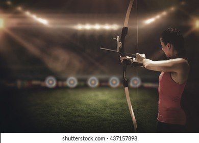 Side view of woman practicing archery on a sports field