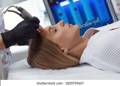 Side view of woman receiving microdermabrasion therapy on forehead at beauty spa
