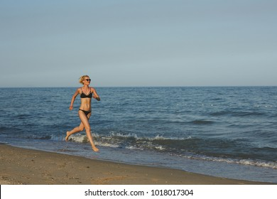 Side view of a woman running on the beach with the horizon and sea in the background
