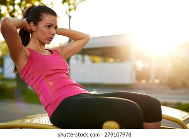 Side view of woman sitting on a bench outside doing situps with hands behind head.