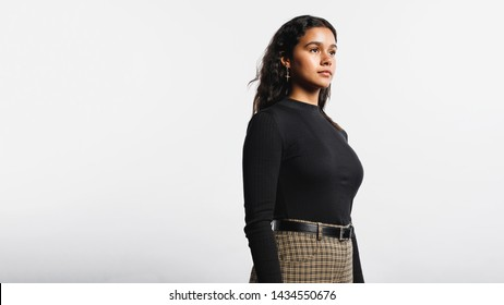 Side view of woman standing against white background. Portrait of young woman looking away.
