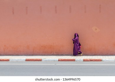 Side view of a woman walking down a Marocco streets