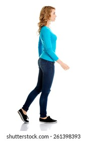 Side view of a woman walking slowly.