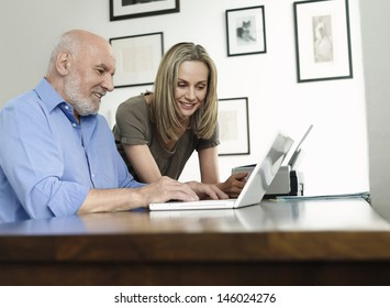 Side view of woman watching mature man use laptop at home office