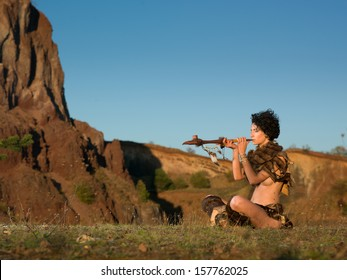 side view of woman wearing fur handmade tribal clothes sitting on the ground and smoking from a peace pipe in nature