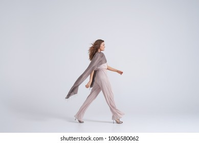 Side view of woman wearing trend clothing and silk scarf walking