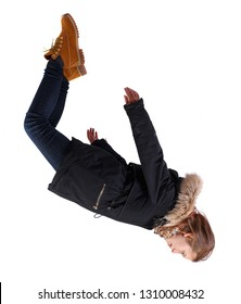 Side view of woman in winter jacket in zero gravity or a fall. girl in parka is flying, falling or floating in the air. Isolated over white background. The girl in winter clothes falls down.