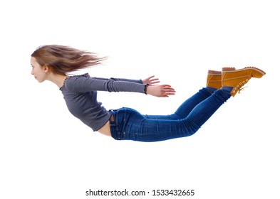 Side view of woman in zero gravity or a fall. girl is flying, falling or floating in the air. Isolated over white background. A young girl in jeans and boots is flying in the air.