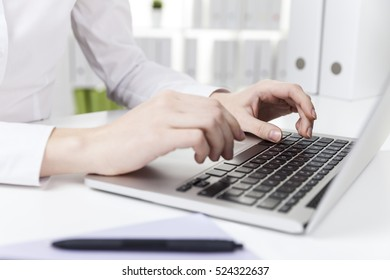 Side view of woman's hands with short nails who is typing in office at her laptop keyboard. Concept of secretary job