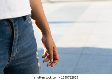 Side view of a womans thigh wearing denim jeans and white shirt with her arm and hand down beside her leg - Female body midriff shot of her waist and stomach and a sunlight backlight with copy space