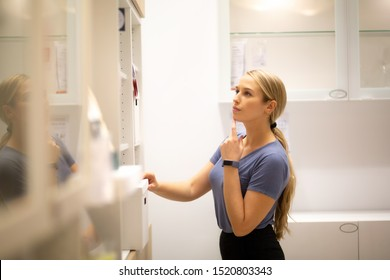 Side view of women standing and looking something on shelf