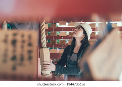 side view from wooden shrine of japanese woman pulling hand touching shimenawa rope make suzu bell at historic wooden temple. girl with hat carrying camera praying in shitennoji shinto osaka japan