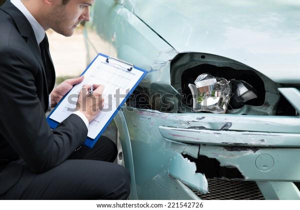 Seitenansicht des Schreibens auf der Zwischenablage bei Versicherungsvertretern, die das Fahrzeug nach einem Unfall prüfen