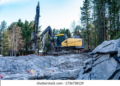 Side view at yellow drilling machine which stands on granite rock and boring holes for dynamite at rock blasting area - further rock exploding, new road construction. Evening shadows, green forest