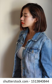 side view young adult asian woman, red lip and short hair in blue jean with beauty face and looking away with white wall