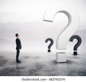 Side view of young adult businessman looking at question marks on abstract foggy gray background. Doubt concept. 3D Rendering