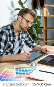 Side view of young adult freelancer using graphic tablet and stylus pencil, sitting behind table, working on the computer, drawing sketch  and editing image