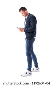 Side view of young adult man walking and looking at mobile phone. Full body isolated on white background.