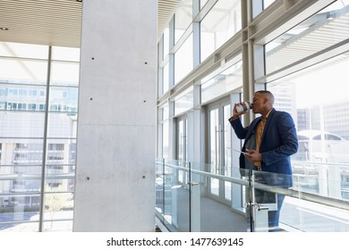 Side view of young African American businessman drinking a takeaway coffee standing on a mezzanine in a bright modern business building. Modern corporate start up new business concept with