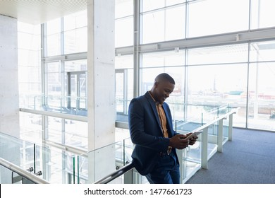 Side view of young African American businessman using a tablet computer standing on a mezzanine in the atrium of bright modern business building. Modern corporate start up new business concept with