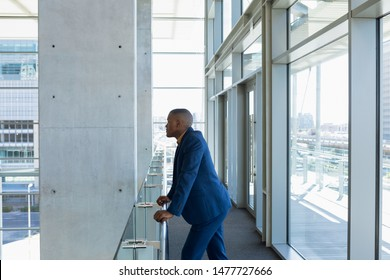 Side view of young African American businessman standing on a mezzanine leaning handrail in the atrium of a bright modern business building. Modern corporate start up new business concept with