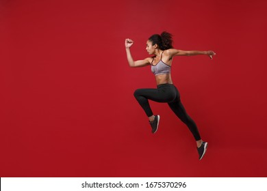 Side view of young african american fitness woman in sportswear posing working out isolated on red wall background studio portrait. Sport exercises healthy lifestyle concept. Jumping like running