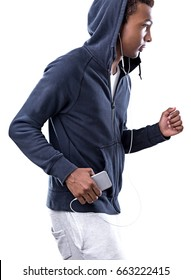 Side view of a young African American sportsman wearing a dark blue hoodie and white sweat pants. He is jogging and listening to music with his smartphone in hands. Isolated portrait.