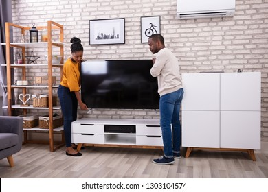 Side View Of Young African Couple Lifting Television At Home