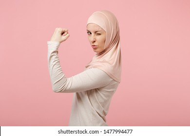 Side view of young arabian muslim woman in hijab light clothes posing isolated on pink wall background. People religious Islam lifestyle concept. Mock up copy space. Blinking, showing biceps, muscles