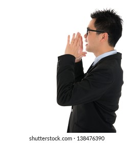Side view young Asian business man shouting with hands cupped to his mouth, isolated on white background