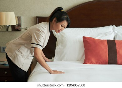 Side view of young Asian woman working in hotel and making bed arranging blanket in daylight