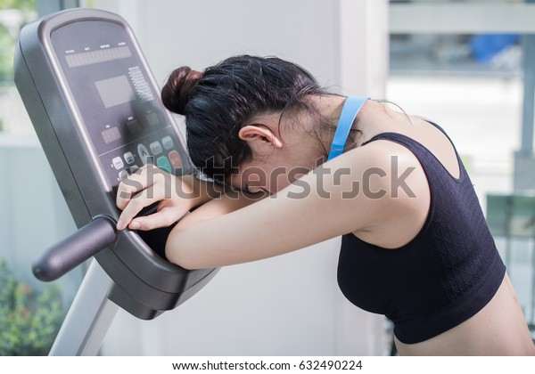 Side view of Young asian woman tired after intense workout on the exercise bike at the gym. Relaxing her muscles after workout in fitness club.