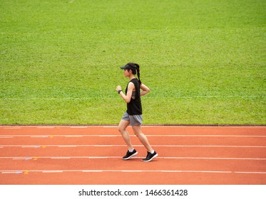 Side view of young athlete runner woman running in the running track in stadium. Running track is a rubberized artificial running surface for track and field athletics.