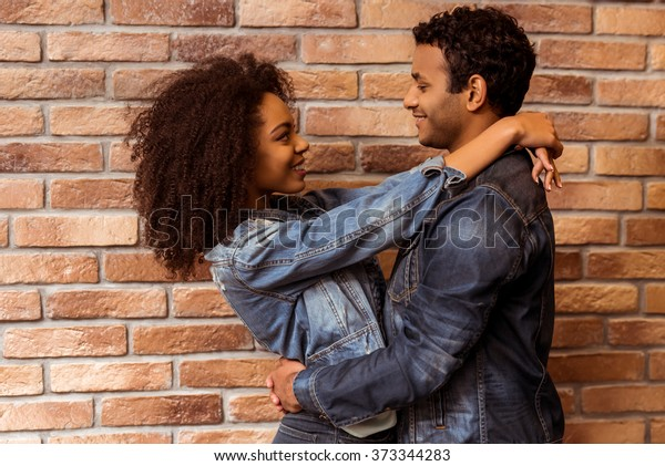 Side view of young attractive Afro-American couple hugging, looking in camera and smiling while standing against brick wall