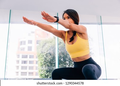Side view of young attractive Asian fitness woman in sportswear doing deep squat at gym