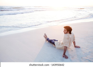 Side view of a young attractive man relaxing sitting down on the shore of a white sand beach at sunset, with the waves bathing the shore in an idyllic nature location, being thoughtful.