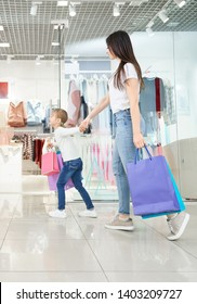 Side view of young attractive mother shopping together with little daughter in mall. Positive girl keeping hand of woman and running in shops. Family choosing and buying new clothes and toys.
