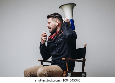 Side view of young attractive movie director shouting on the megaphone while sitting on the chair isolated on grey background. Man directing film process
