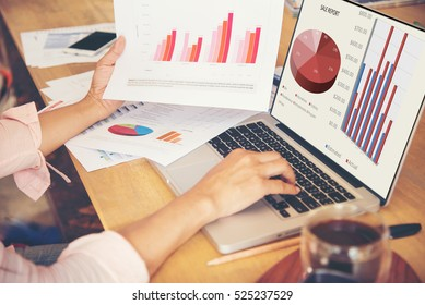 Side view of young Audit Woman using laptop and reading annual report , Accounting Graph and document at office. Display Sale report and graph on notebook.