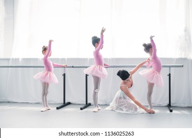 side view of young ballet teacher exercising with kids in ballet school