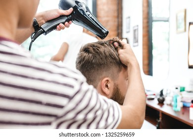 Side view of young bearded man getting groomed at hairdresser with hair dryer while sitting in chair at barbershop. The moment of styling hair dryer bearded man in the bright space of the barbershop