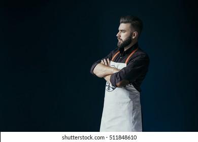 Vue latérale. Un jeune homme barbu, vêtu d'une chemise brune foncée et d'un tablier clair, se tenant debout avec son dossier d'armes. Sur fond bleu foncé, mur.