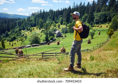 Side view of young bearded man admiring view of mountains. Looking at beautiful mountains inspirational landscape