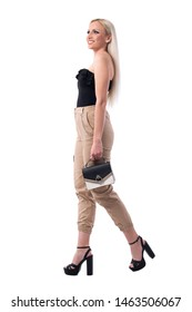 Side view of young beautiful blonde woman walking with bag watching and shopping. Full body isolated on white background.