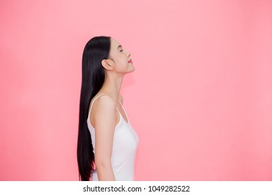 Side view of Young beautiful and calm Asian woman isolated over pink background