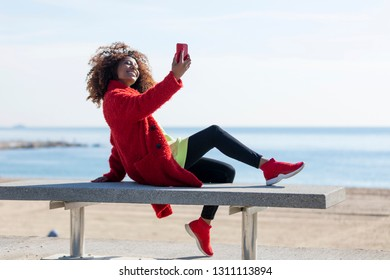 Side view of young beautiful curly african american woman sitting on a bench at beach while using a mobile phone to take a selfie outdoors